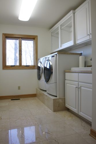 Natural stone flooring in a laundry room space.
